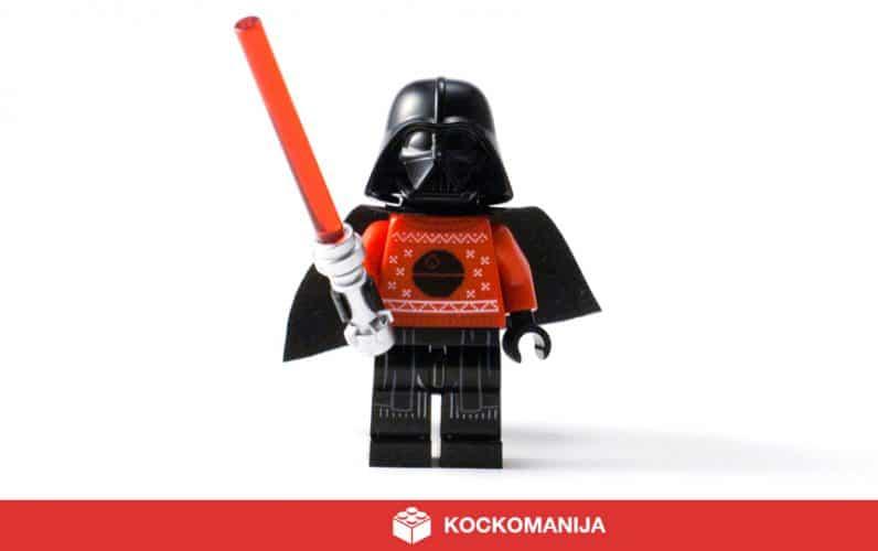 Čudovita minifigura LEGO Darth Vader z rdečim svetlobnim mečem v desnici. Na sebi ima rdeč pleten pulover s črno zvezdo smrti in mini Tie Fighterji. Zelo posrečeno. Praznično.