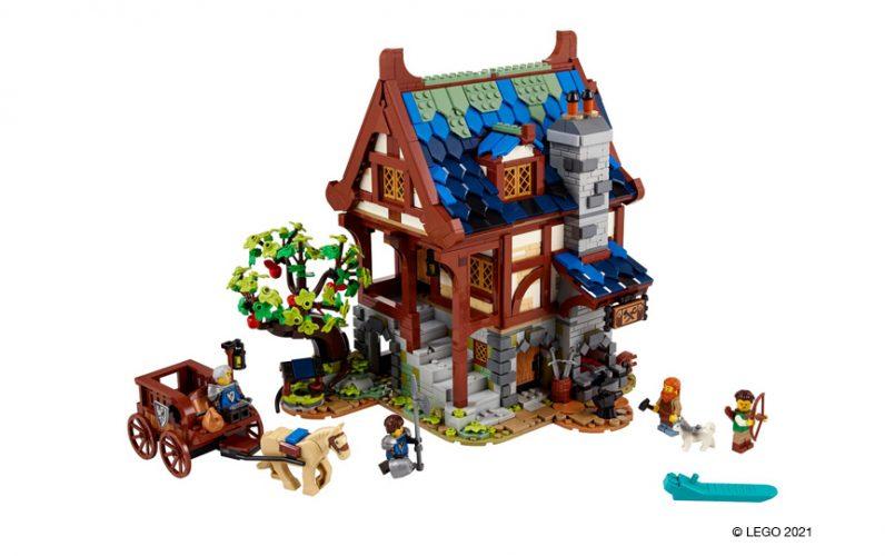 Model 21325 LEGO Ideas Srednjeveške kovačnice. Pred njo je konska oprega z vitezom in še enim vitezom, ki teče na popravilo čelade.