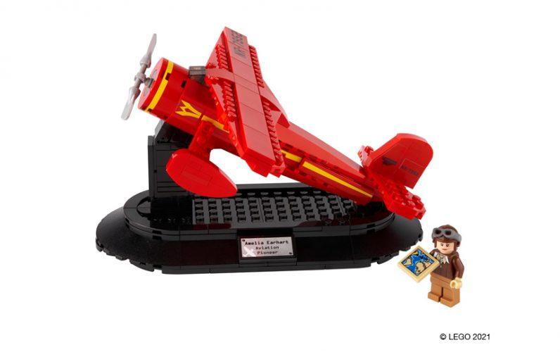 40450 LEGO Rdeče letalo Amelie Earhart na črnem podstavku s plaketo. Poleg stoji ekskluzivna minifigura Amelia Earhart, ki v roki drži zemljevid.