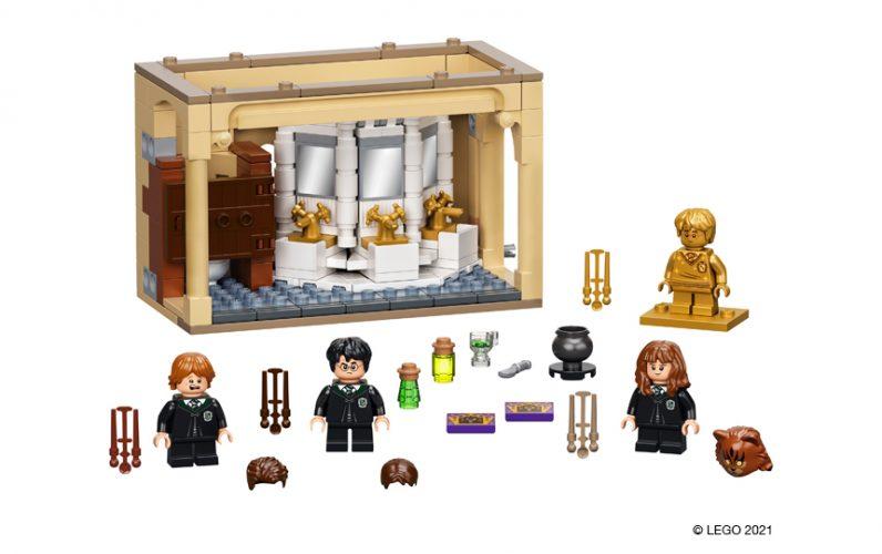 Harry Potter, Ron Weasley in Hermiona Granger pred skupnimi umivalniki v sanitarijah. Vsak ima svojo palico, Hermiona ima zamenljivo glavo kot muca.