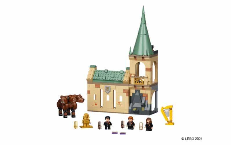 Troglavi pes Miško, Harry, Ron in Hermiona pred delom obzidja Bradavičarke s stolpom.