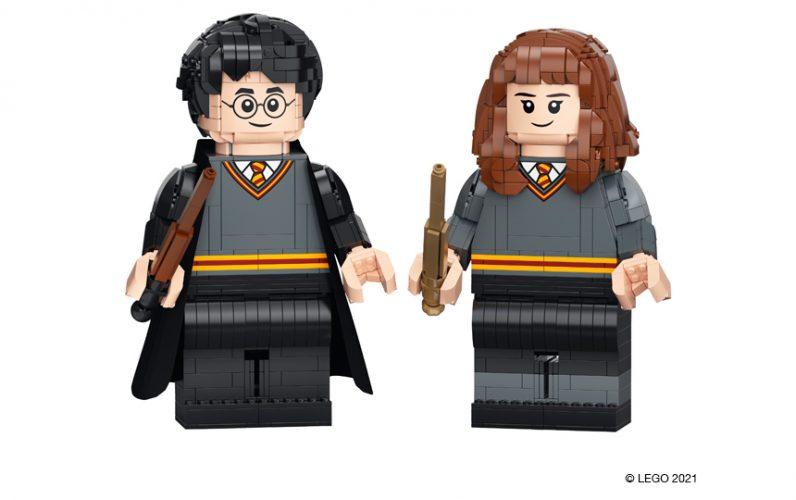 Veliki figuri Harryja Potterja in Hermione Granger sestavljeni iz več kock. Oblečena sta v šolsko sivo-črno uniformo. V rokah držita palici.