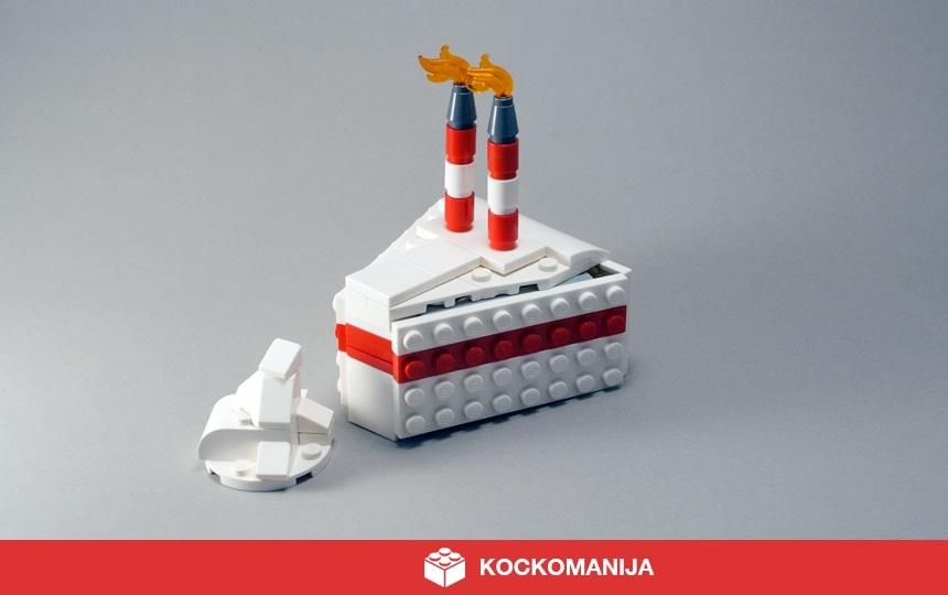 Kos bele smetanove torte iz LEGO kock. 2 prižgani svečki. Kupček smetane.