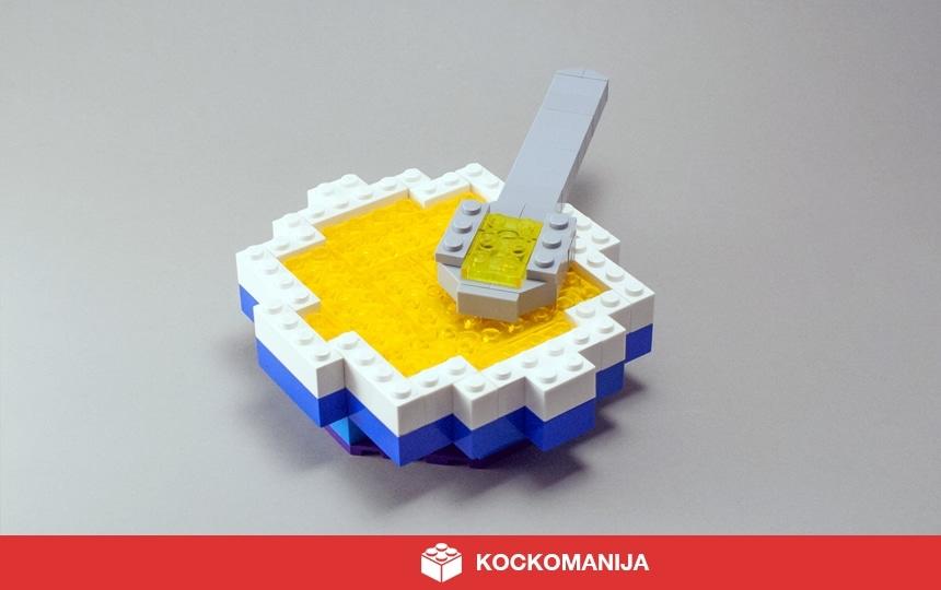 Keožnik goveje juhe iz LEGO kock. Na krožniku je žlica polna juhe.