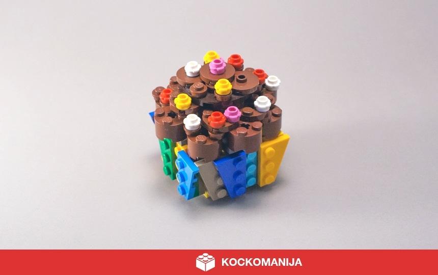 Čokoladni muffin okrašen z barvnimi mrvicami v pisani posodici.