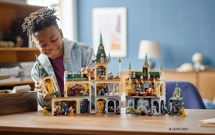 LEGO Harry Potter - deček se igra za mizo s sestavljenimi seti novih LEGO Harry Potter