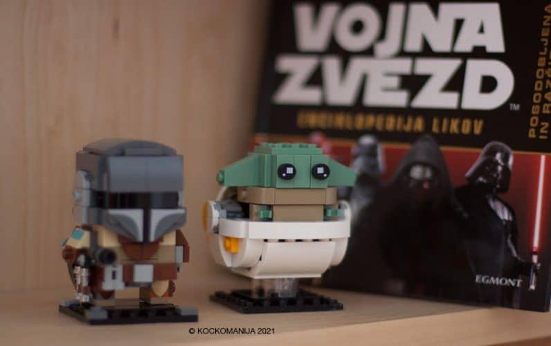 Mandalorian in Baby Yoda v vozičku na polici. V ozadju knjiga Vojna zvezd.