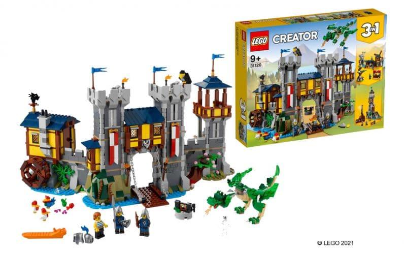 LEGO srednjeveški grad iz kock. Spredaj zeleni zmaj iz lego kock. V ozadju rumena LEGO škatla srednjeveškega gradu