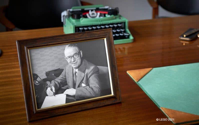 Ole Kirk Kristiansen na fotografiji. V ozadju pisalni stroj iz LEGO kock.
