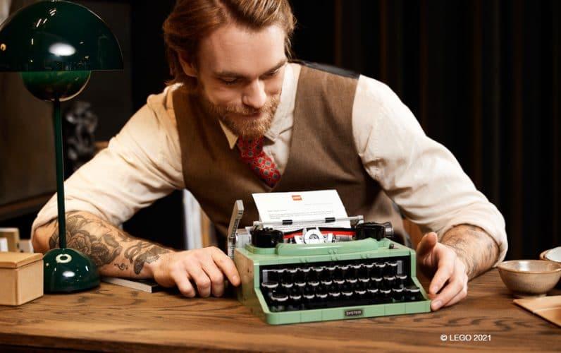Moški z brado sedi za mizo in občuduje pislani stroj iz LEGO kock