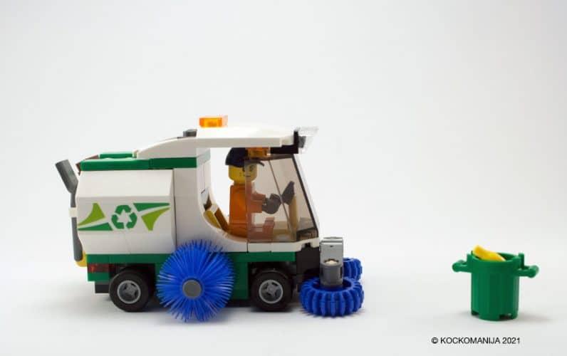 Cestni pometač pred zelenim košem za smeti v katerem je banana
