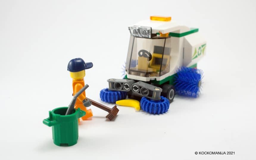 Cestni pometač iz LEGO kock. Pred njim možiček z metlo in banano.