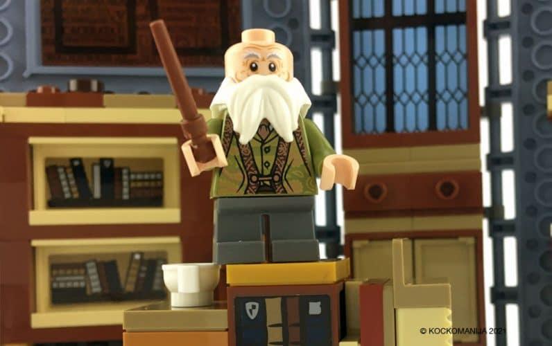 LEGO minifigura Profesor Colibri s palico v roki stoji na mizi